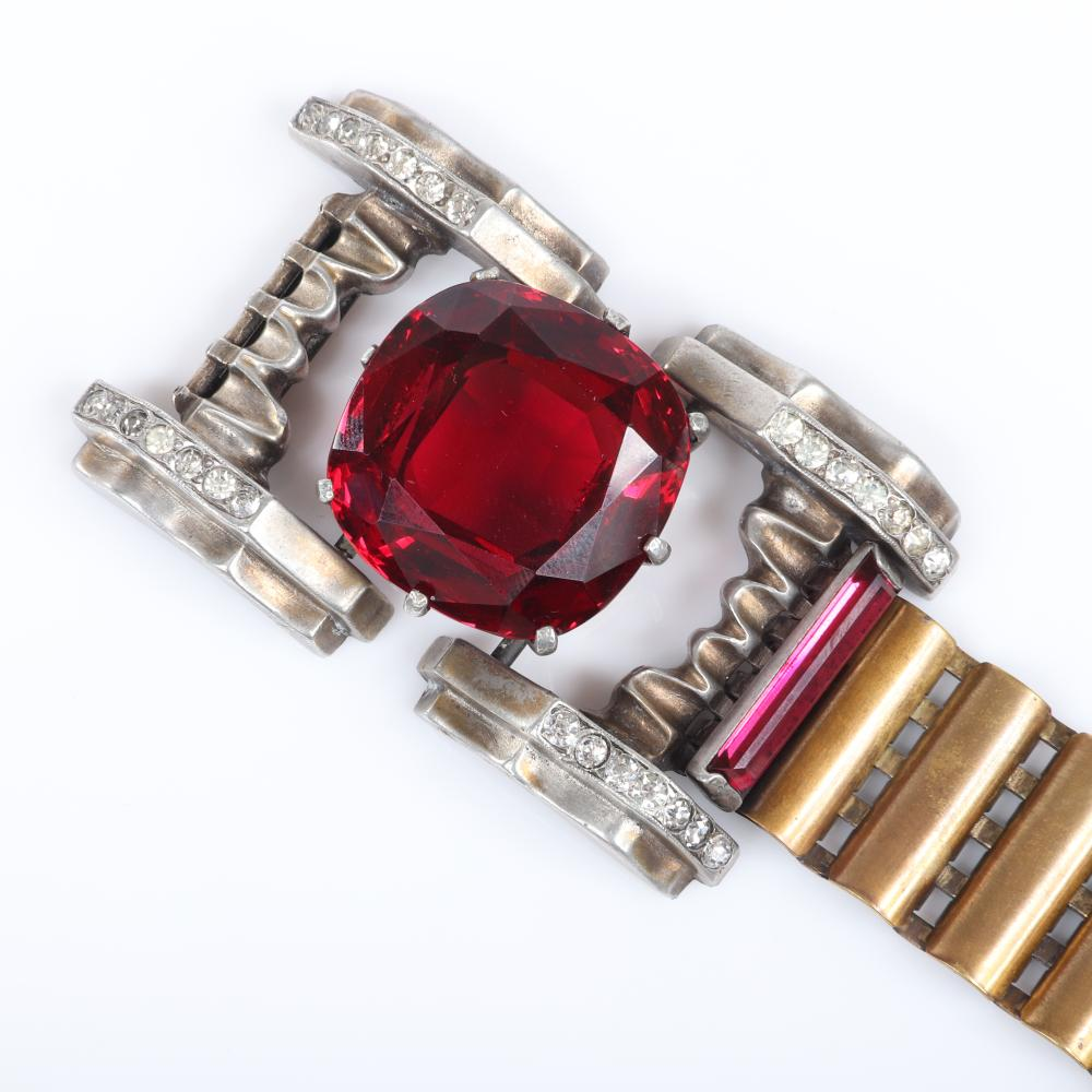 "Eisenberg Rare unsigned Deco bracelet in gold washed pot metal with huge 1 1/8"" ruby central crystal and two 1"" baguettes, antiqued gold panel links and pave details. 7 1/2""L x 1 5/8""W"