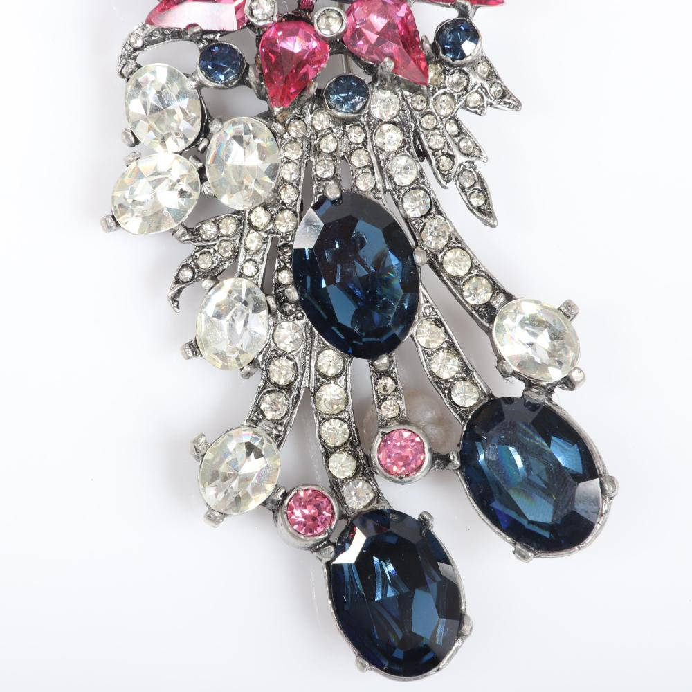 "Eisenberg Original large dramatic floral spray pin with huge sapphire oval and emerald-cut crystals, deep pink teardrop stones, clear and blue bezel-sets and pave, c. 1940s. 4 1/2"" x 3"""