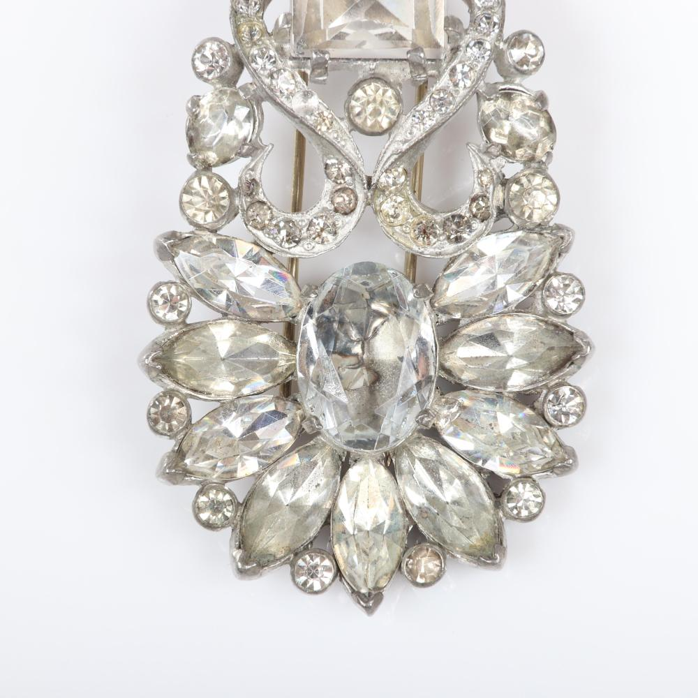 "Eisenberg Original floral pin clip in pot metal with large colorless faceted crystal jewels, diamante, and rhinestones, with setter's mark, c. 1940s. 2 3/4"" x 1 1/4"" (clip), 3/4""H (oval and emerald cut crystal)"