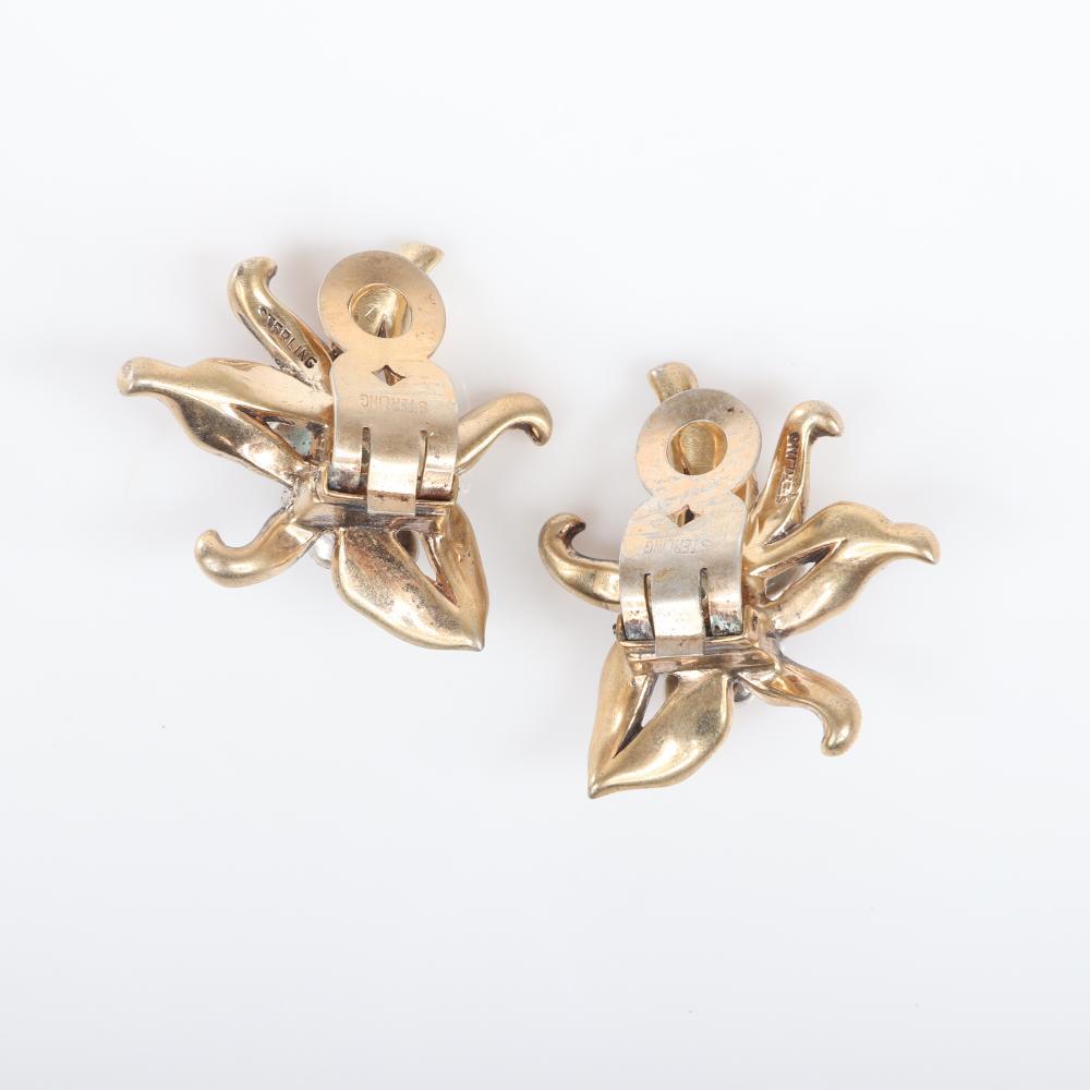 "Eisenberg Original sterling vermeil dimensional orchid clip earrings with curling petals, pave rhinestones surrounding a sapphire blue baguette, c. 1948. 1"" x 1"" (each)"