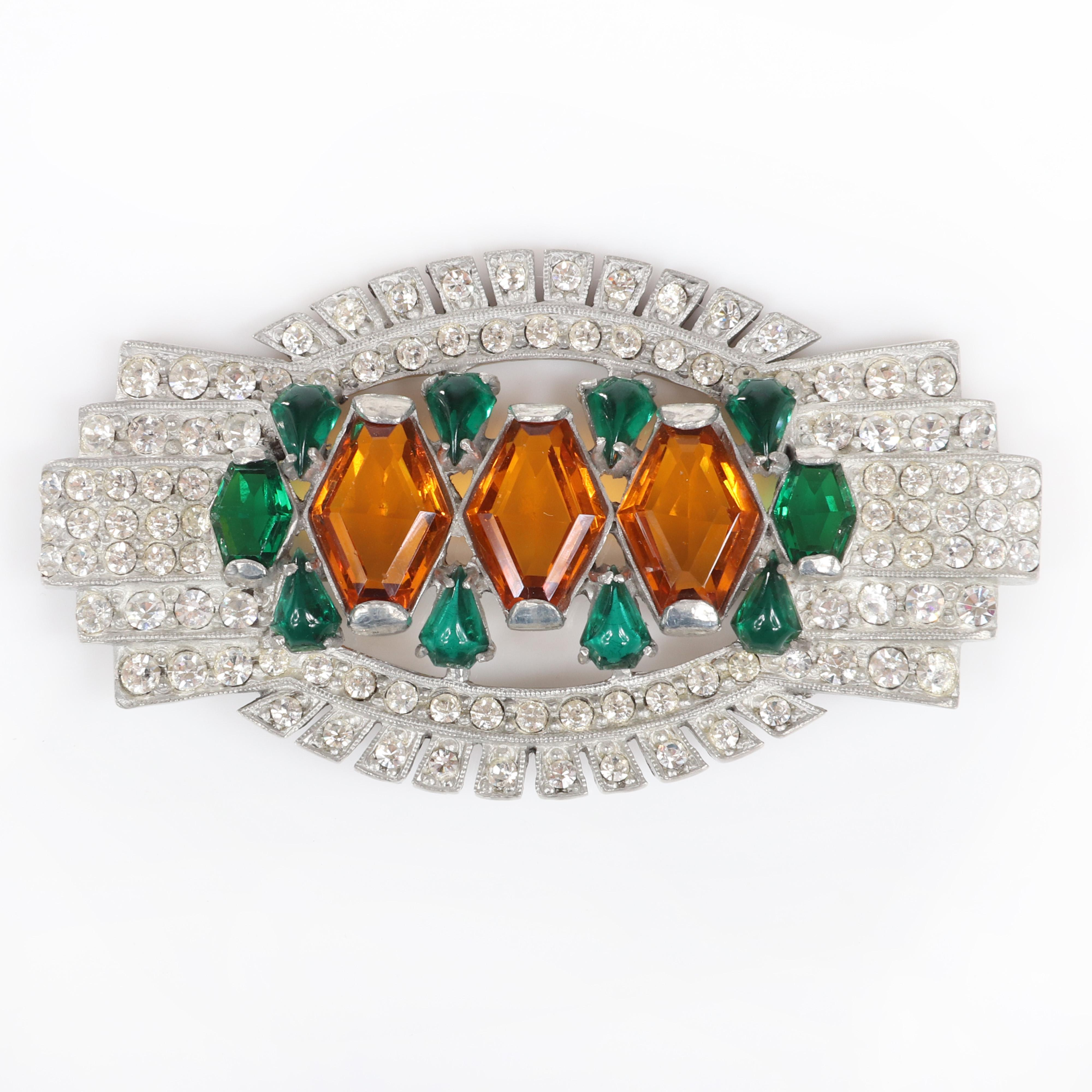 "Eisenberg Art Deco brooch in silver pot metal and three large topaz crystals surrounded by green teardrop stones and pave with openwork highlights, mid to late-1930s. 1 7/8"" x 3 5/8"""