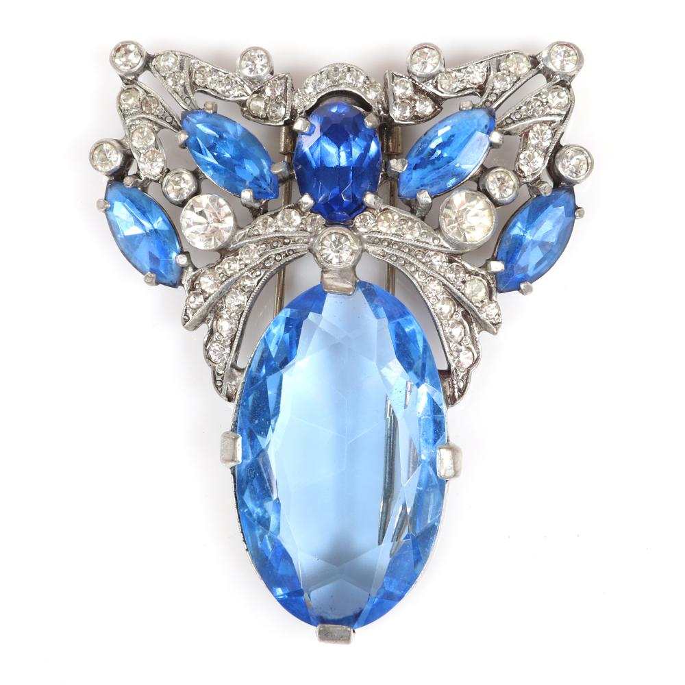 "Eisenberg Original stunning fur clip with massive blue glass open backed crystal drop, pave and bezel-set clear ribbons highlighted by blue open-backed stones, c. 1940. 3"" x 2 1/4"""