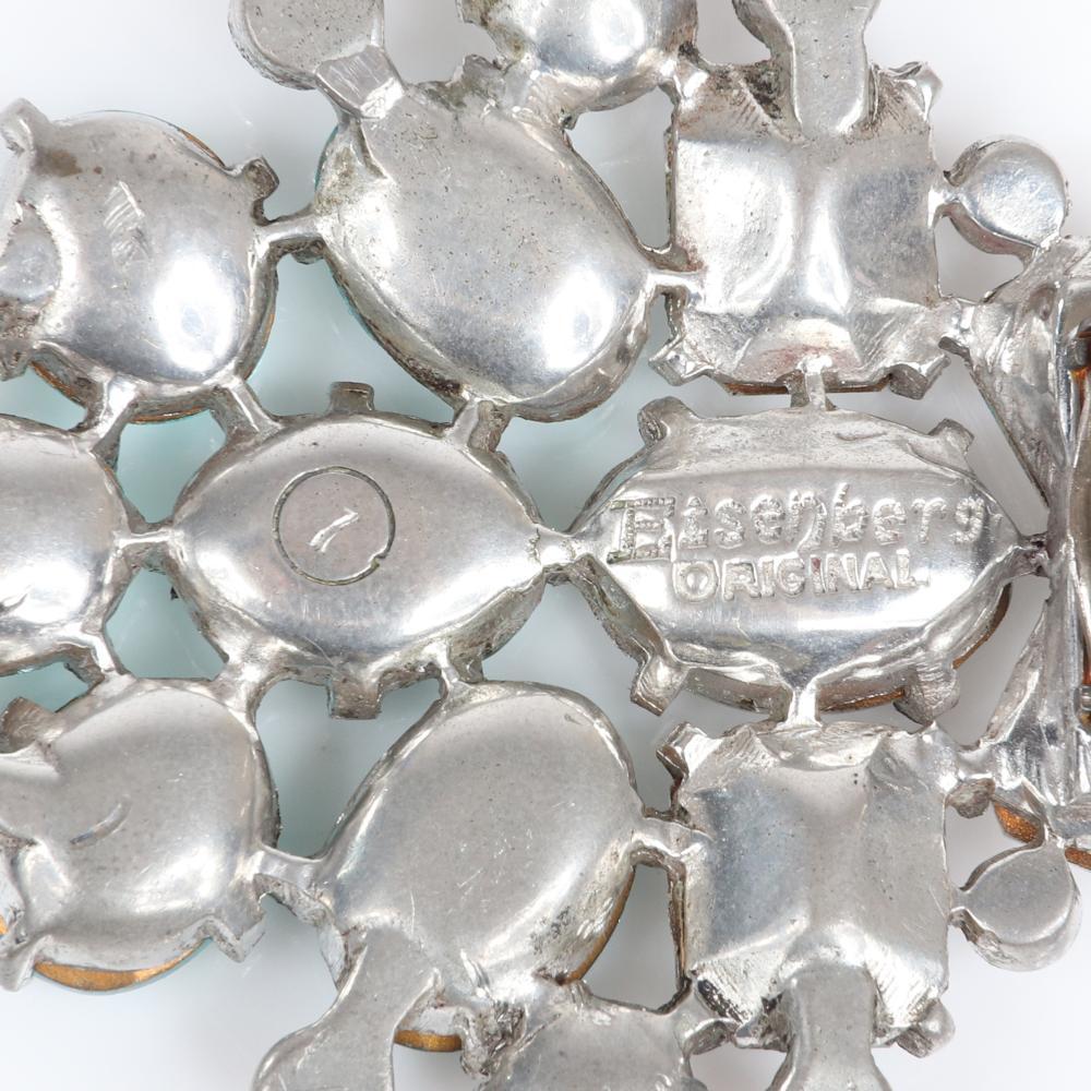 "Eisenberg Original aqua and clear stone dress clip in silver pot metal with large clear emerald-cut, aqua oval-cut stones and bezel-set accents, c. 1940. 2 1/8"" x 2"""