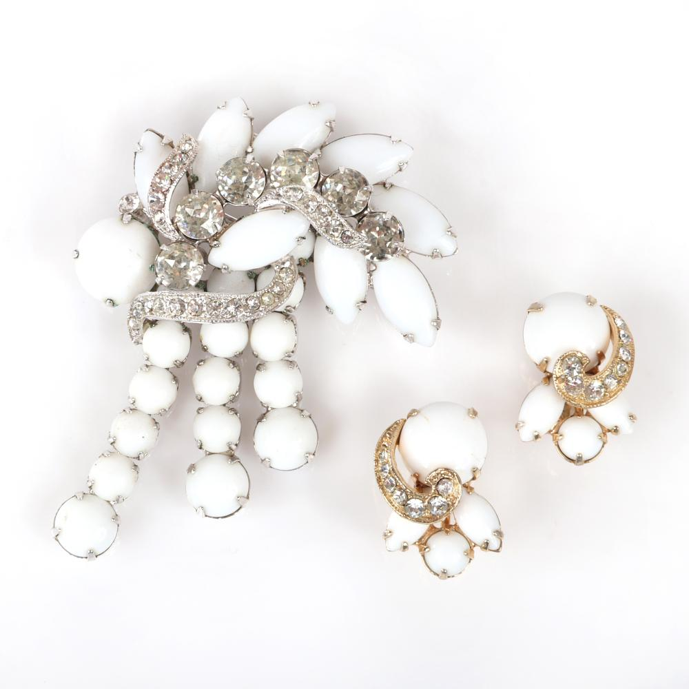 """Eisenberg Ice rhodium-set milk glass and diamante dangling ribbon pin and earring group, marked Block Eisenberg, 1950s. Includes original Vogue advertisement. 2 1/2"""" x 2"""" (brooch), 1"""" (earrings)"""