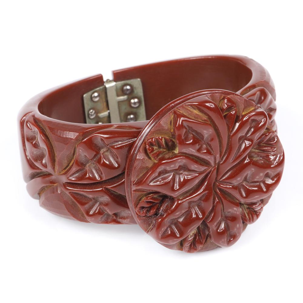 "Bakelite wide red brown clamper cuff with heavily carved round floral leaf design on bracelet and applied medallion. 2 1/4""inner diam, 1""W, 1 3/4""diam (medallion)"