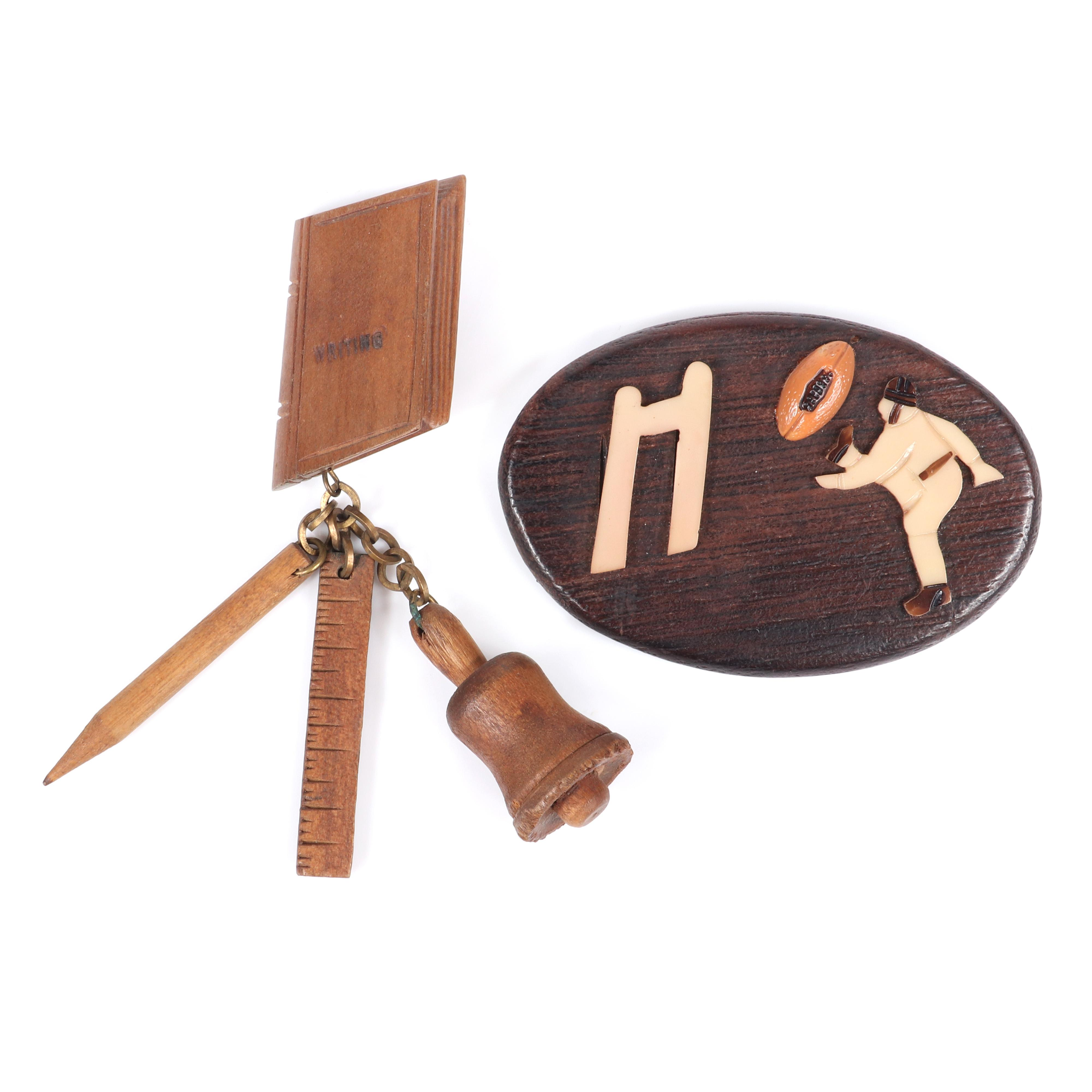 """Two vintage carved wood figural pins: large oval Varsity football themed brooch with celluloid kicker and goal post, with """"School Days"""" book pin with bell, ruler and pencil charms. 2 1/4""""H x 3 3/8""""W"""
