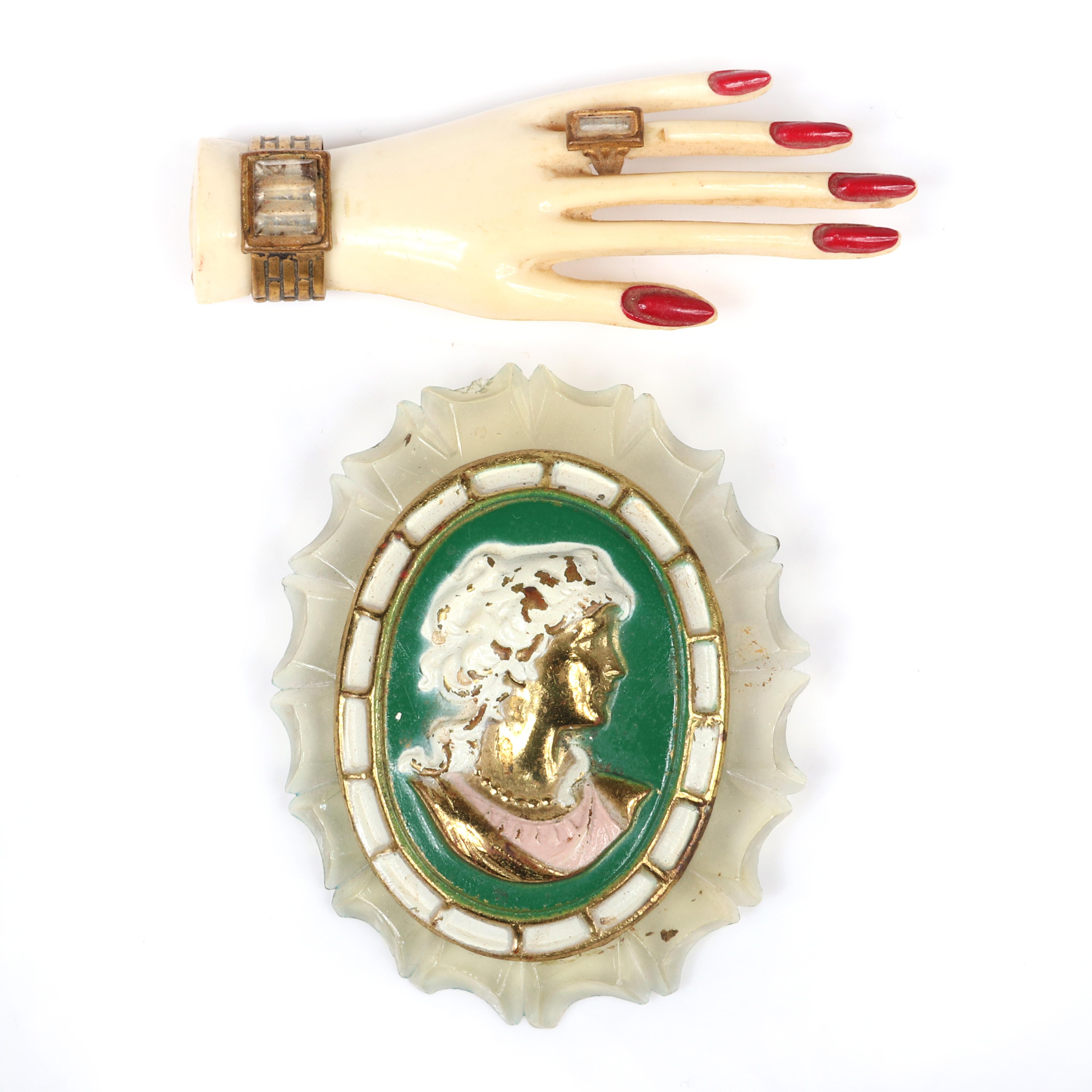 Two vintage retro celluloid pins: Art Deco glamour hand with enameled nails and brass ring and bracelet, with transparent scalloped celluloid and enameled metal cameo pin. 2 x 1 in. (5.08 x 2.54 cm.)