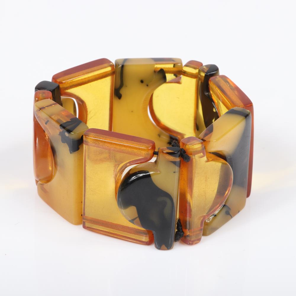 Vintage Bakelite geometric stretch bracelet with alternating interlocking geometric shapes of translucent apple juice and mottled yellow to black tortoise color panels.