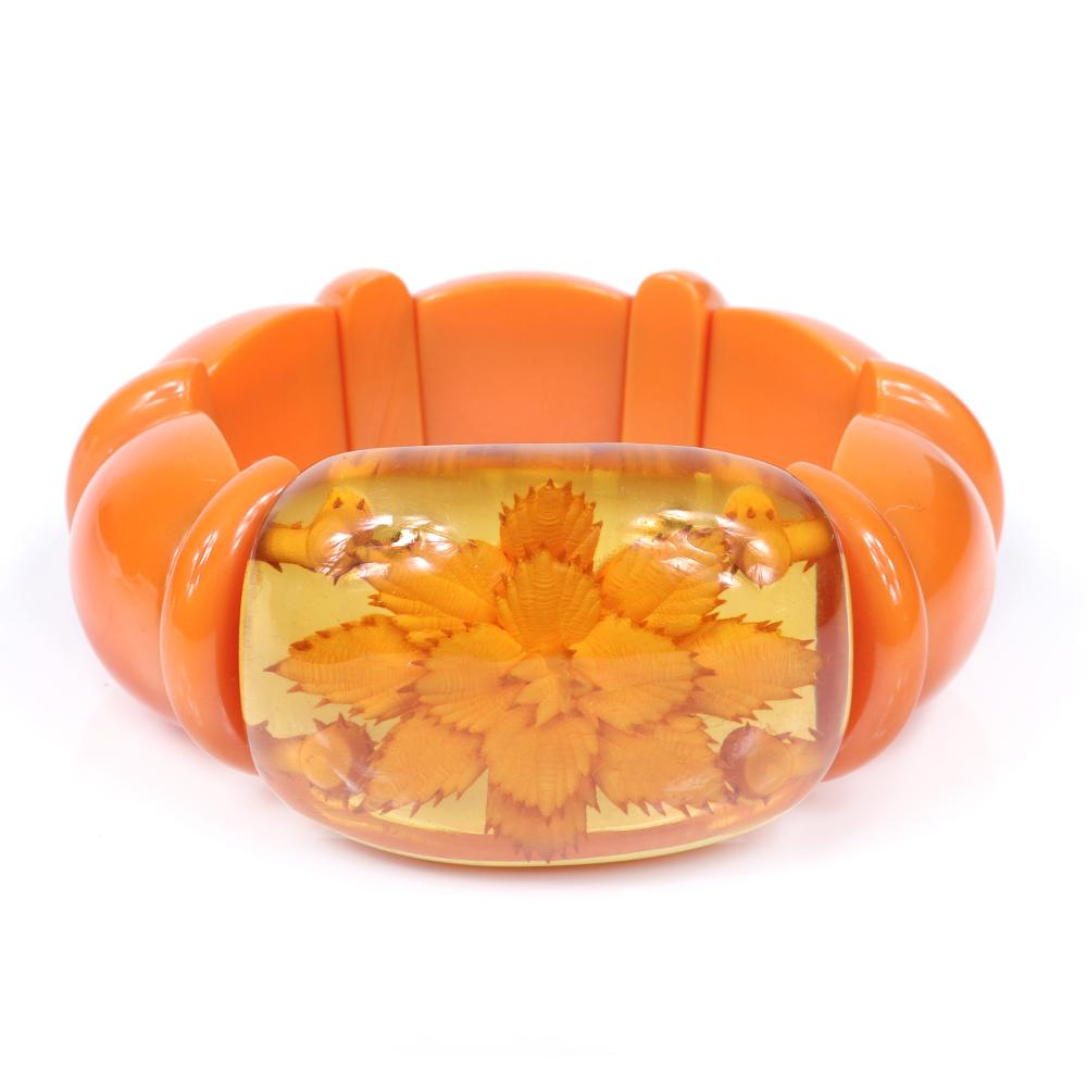 "Vintage Bakelite stretch bracelet with tangerine wedge and line spacers and reverse carved apple juice panel with layered flower. 2"" diam unstretched, 1 1/4""W"