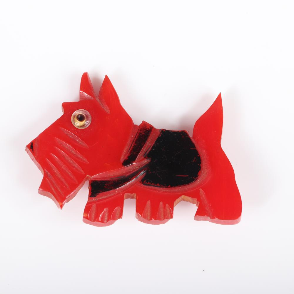 "Two vintage carved Bakelite green and red figural scottie dog pins with glass eyes and painted features. 2""H x 3""W (green)"