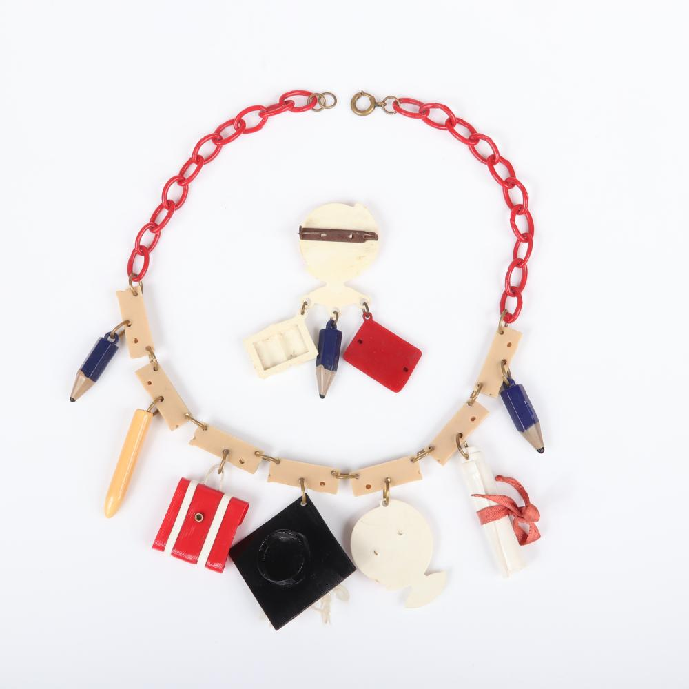 """Vintage celluloid 1950s plastic """"School Days"""" charm jewelry; globe pin and necklace with red chain, linked rulers and pencil, pen, globe, book, diploma, blackboard charms. 16 1/2"""" (necklace), 3""""H (brooch)"""