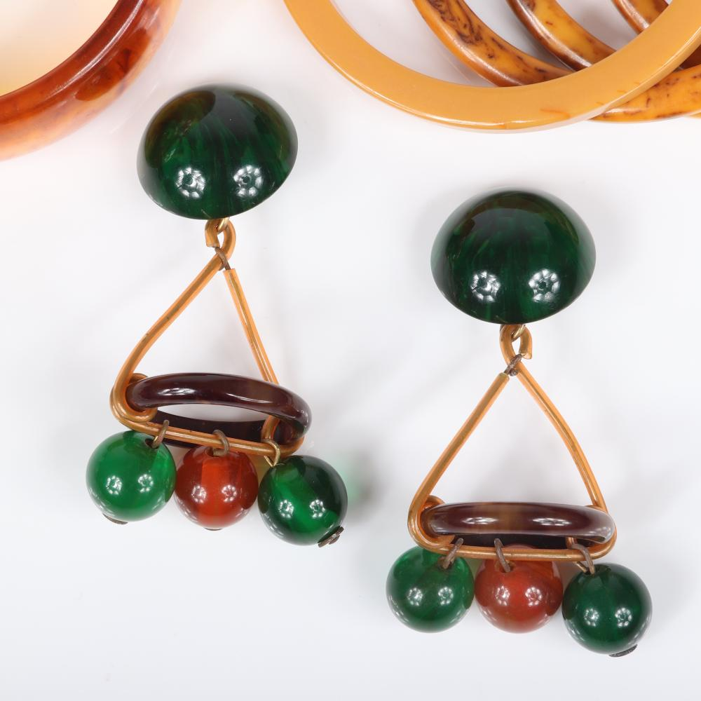 """Six piece Bakelite and lucite plastic jewelry group: four spacer bracelets, one wide bangle bracelet and dangling earrings with green and gold beads. 2 1/4"""" inner diam"""
