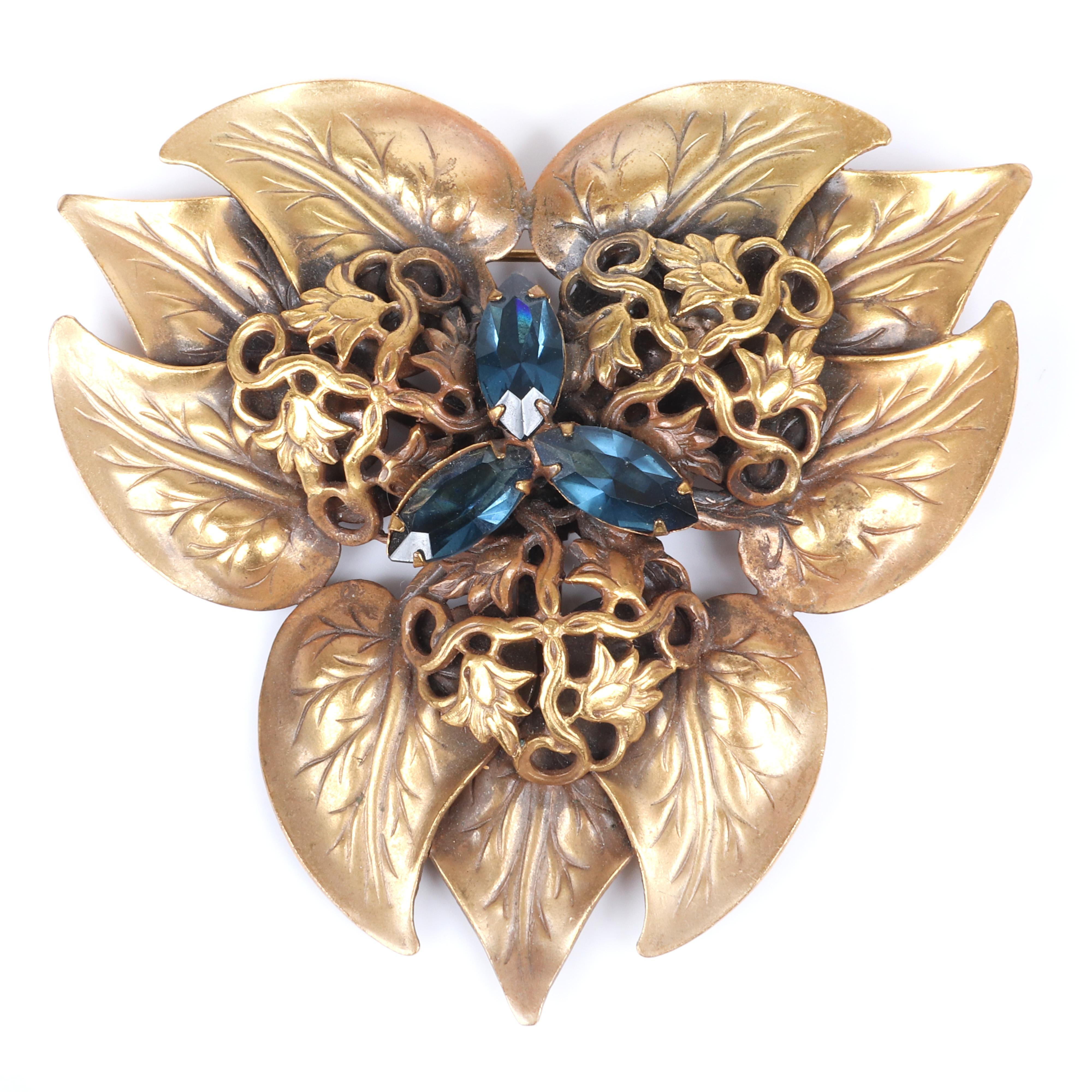 "Joseff of Hollywood large gold tone brooch with layered heart-shaped leaves, openwork fines and three large marquise sapphire crystals. 3""H x 3 1/4""W"