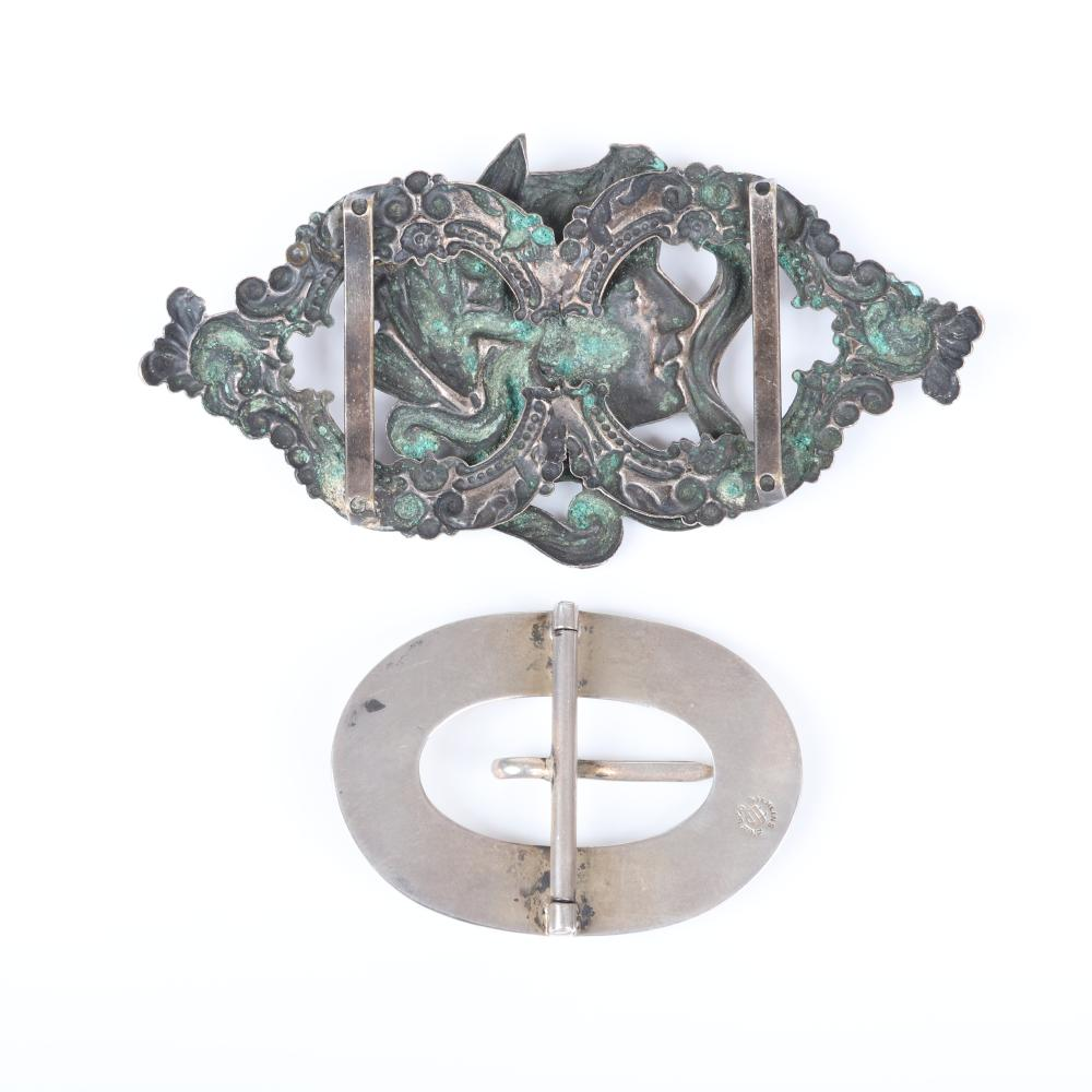 """Two vintage belt buckles: sterling silver oval with six ruby glass cabochons and Nouveau female profile with scrolling frame. 2 1/4""""H x 4 1/2""""W (largest)"""