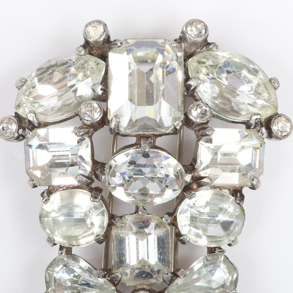"""Eisenberg Original arched dress clip with silver pot metal and two bezel-set rhinestones framing two large clear faceted crystals in different dimensions, late 1930s. 2 1/4"""" x 3/4"""""""