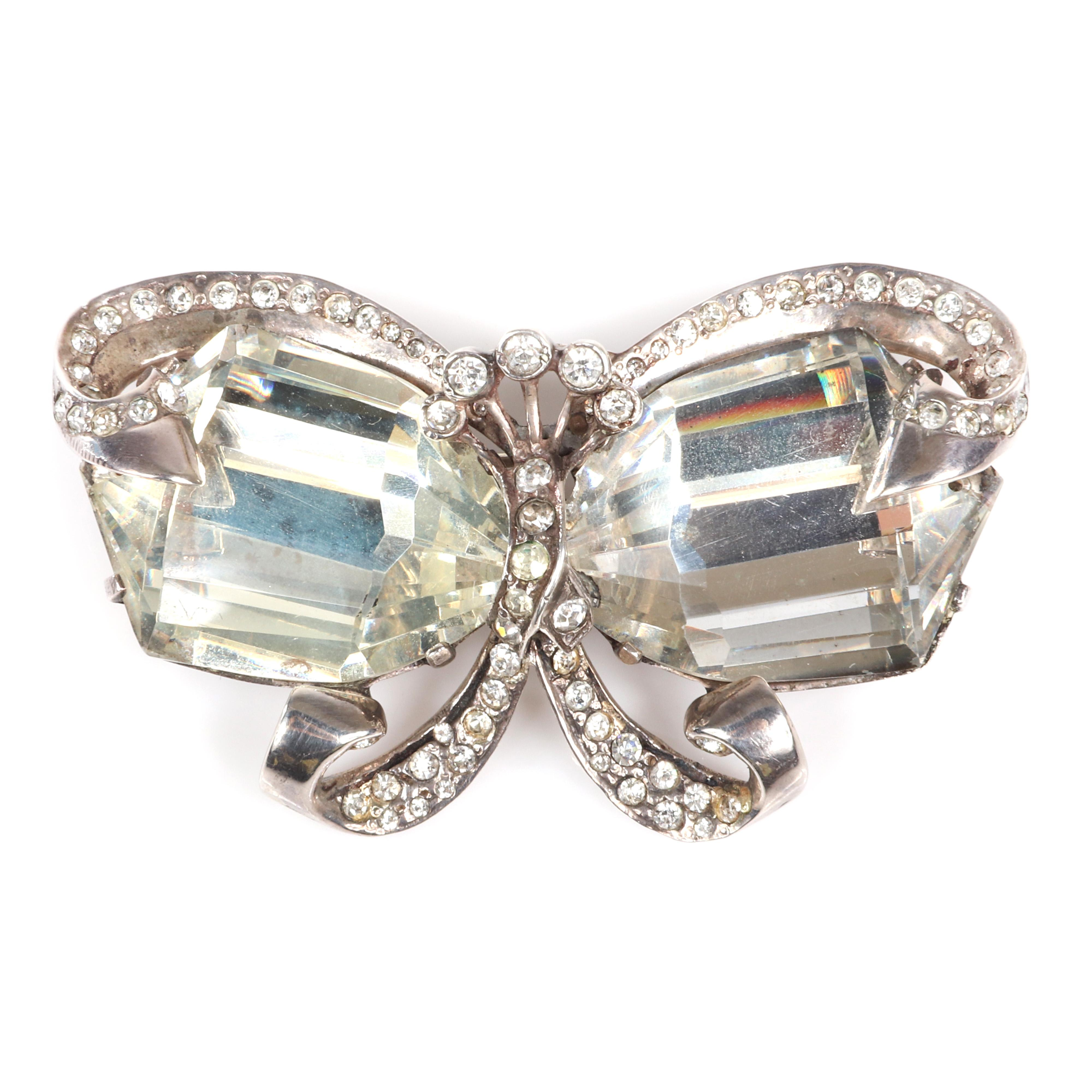 """Eisenberg Original unique sterling bow brooch with two massive, heavily faceted clear crystals and ribbon work decorated with pave and bezel-set top fan, mid-1940s. 2"""" x 3"""""""
