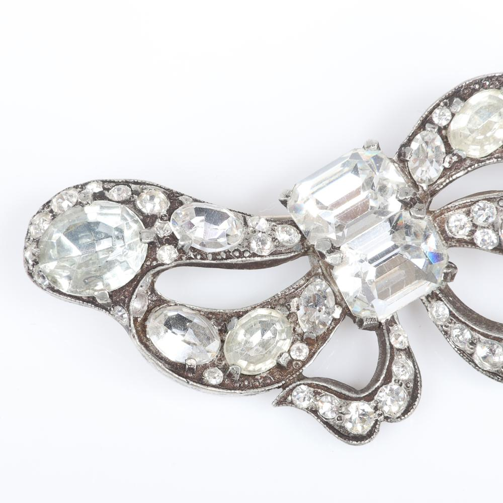 "Eisenberg Original asymmetrical bow brooch with silver pot metal, two large emerald-cut stones form the central knot and oval colorless crystals in various sizes, c. 1940. 1 3/4"" x 3"""