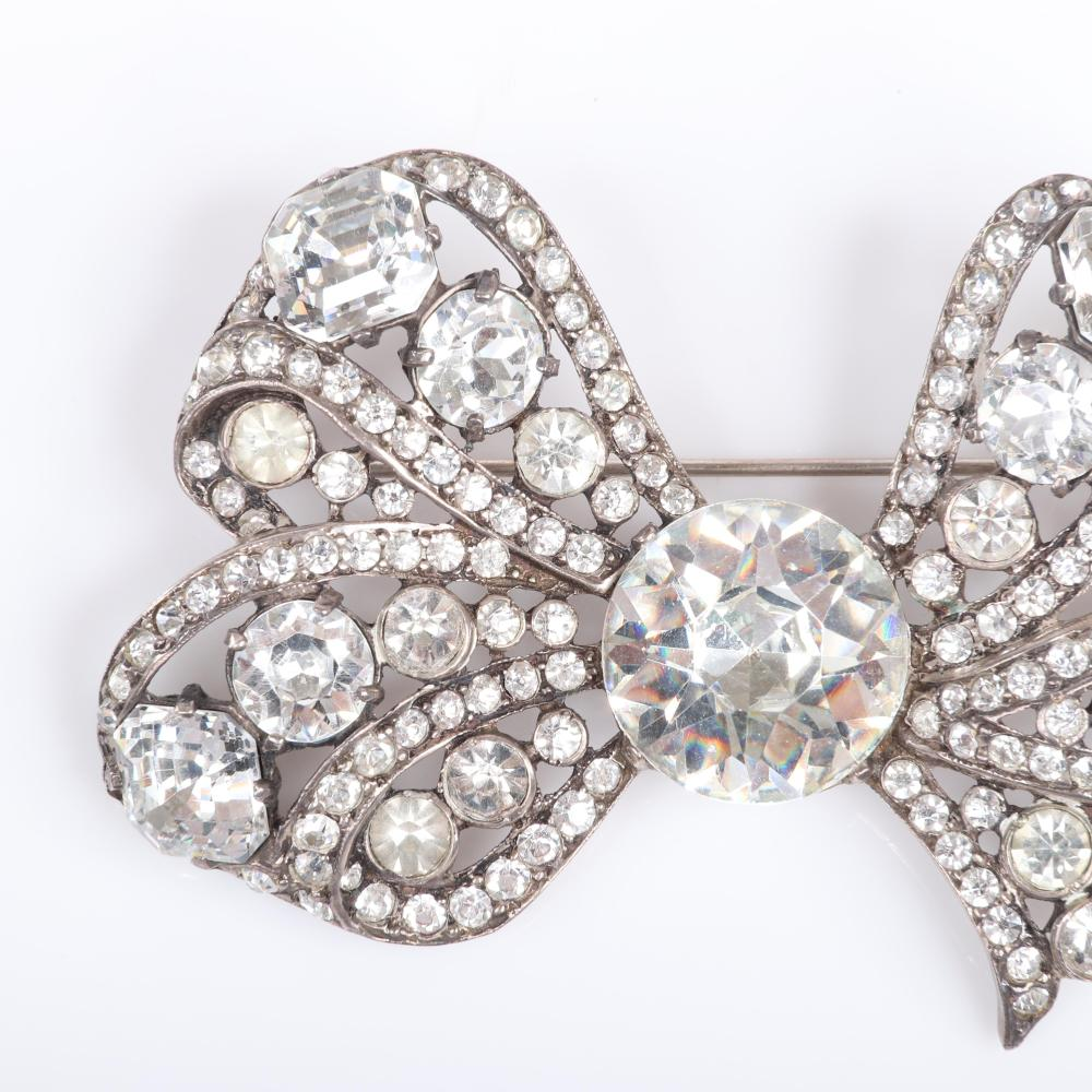 """Eisenberg Original sterling bow brooch with large clear crystal and ribbon loops with large multi-cut prong set rhinestones of various sizes and pave, mid-1940s. 3"""" x 2 1/4"""""""