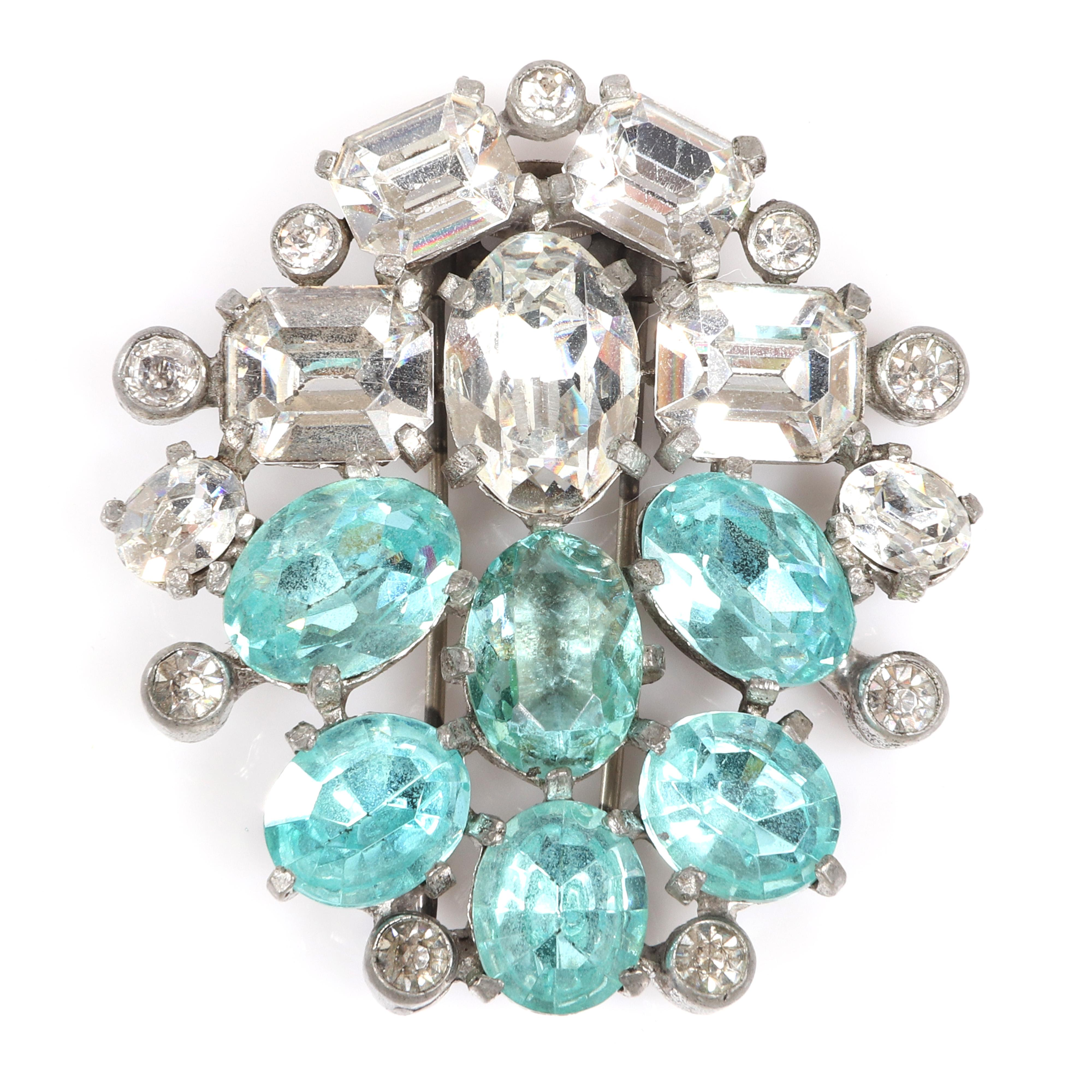 "Eisenberg Original aqua and clear stone dress clip in silver pot metal with large clear emerald-cut, aqua oval-cut stones and bezel-set accents, c. 1940. 2 1/8"" x 2"""