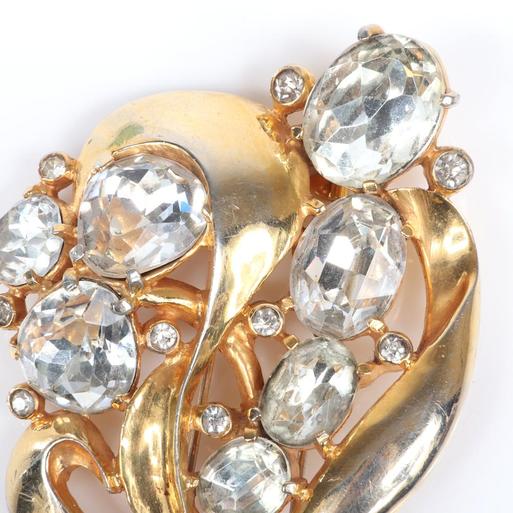 """Eisenberg Original abstract floral fur clip with curving gold washed leaves and oval and pear-set stones and bezel-set accent rhinestones, 1940s. 4"""" x 2 1/2"""""""