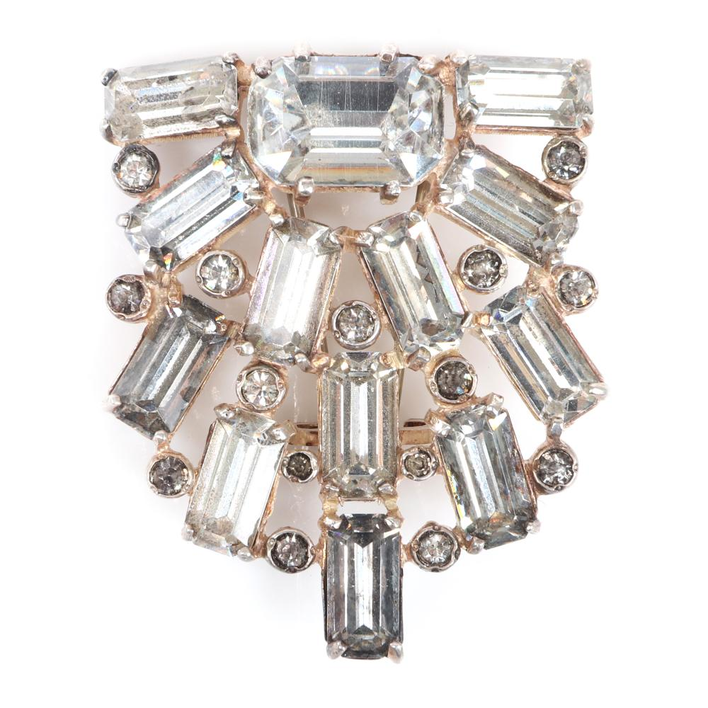 """Eisenberg Original sterling silver, diamante shield shaped fur clip with large emerald-cut crystals separated by bezel-set rhinestones, with script E. 2"""" x 1 3/4"""""""