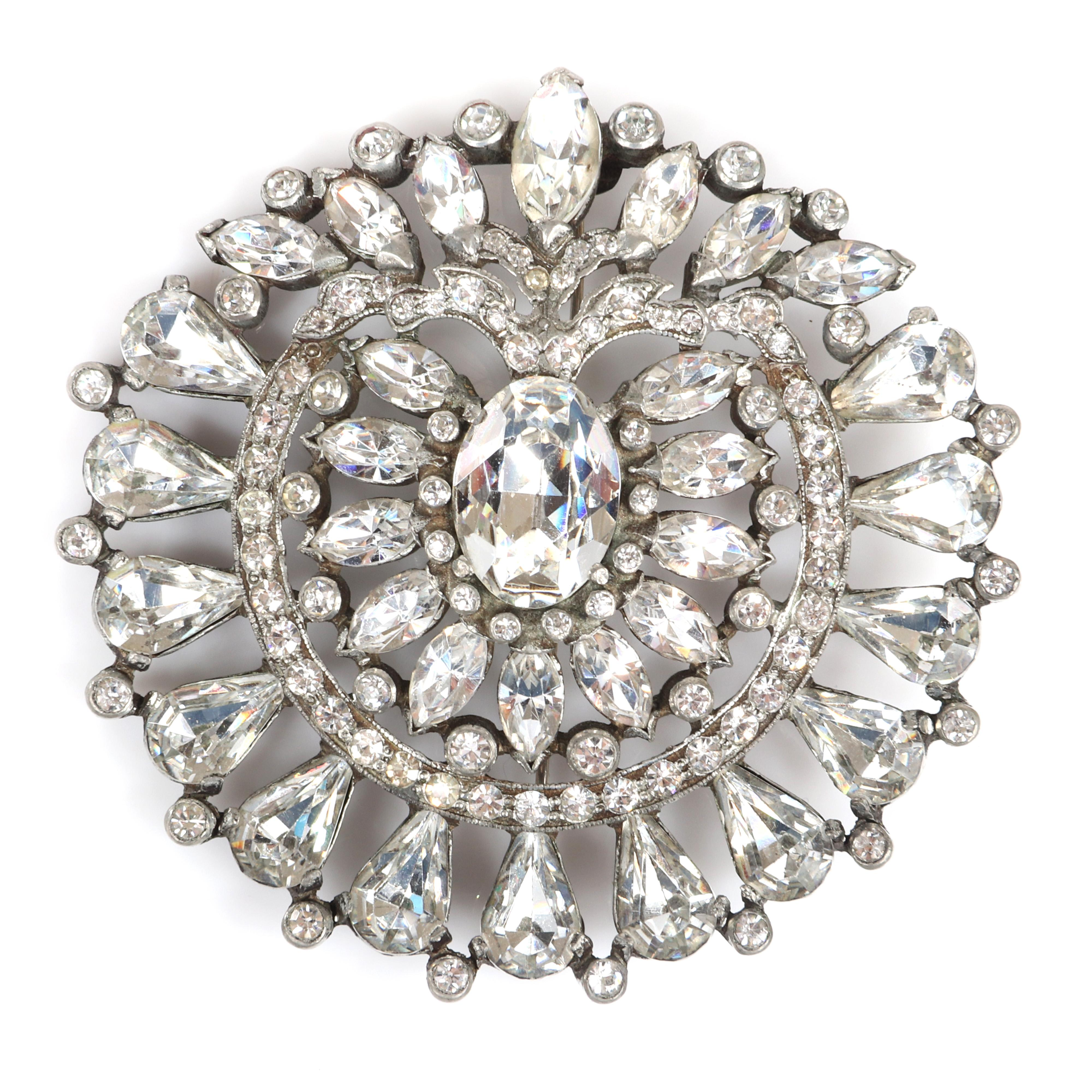 """Eisenberg Original circular brooch with silver pot metal, familiar center design of marquise stones framing a large oval crystal with pear and bezel-set rhinestones, c. 1940. 3"""" diam"""