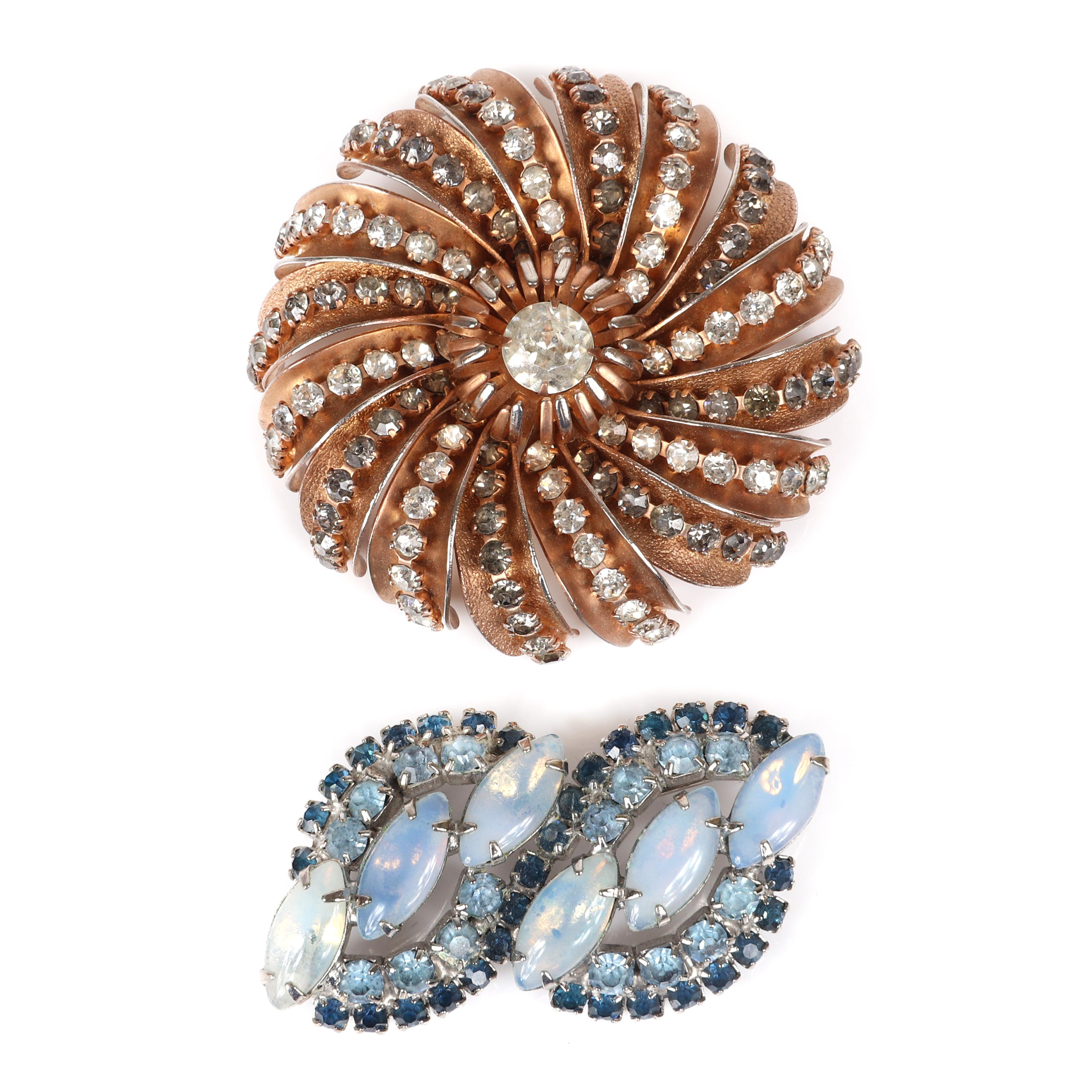 """Two vintage pins: Hobe copper color circular brooch with spiraling lines of rhinestones and unsigned double oval brooch with blue rhinestones and marquise moonstones. 2 1/4""""diam (Hobe brooch)"""
