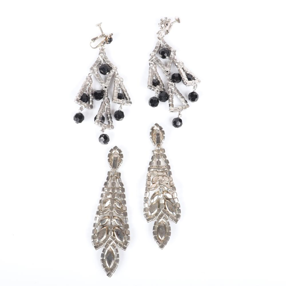"""Two pairs of vintage diamante chandelier earrings: black rhinestone and dangling crystal bead clips and rows of colorless rhinestones with emerald marquise crystals. 3 1/2""""H (black), 3 3/4"""" (green)"""