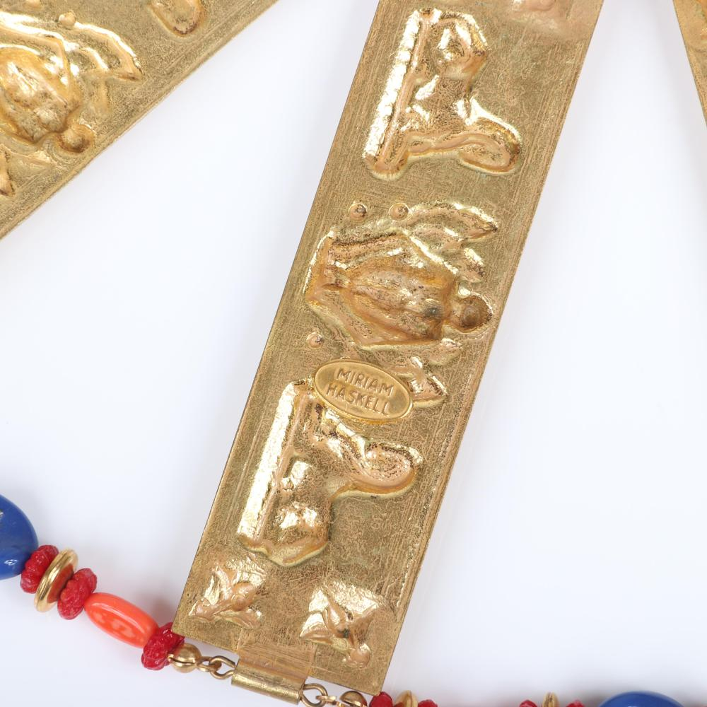 "Miriam Haskell Egyptian Revival gold tone collar necklace and bracelet set with large repousse winged pharaohs wedge links and faux coral, lapis and turquoise glass beads. 16""L (necklace), 8""L (bracelet), 3 3/4""W (eac..."