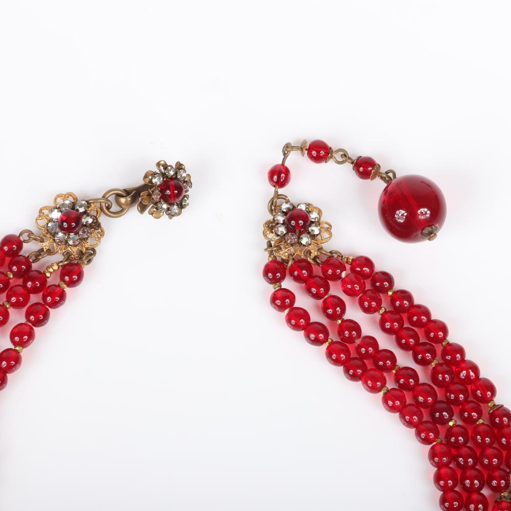 Miriam Haskell 2pc. set; four-strand choker necklace with ruby red glass beads and domed floral cluster pendant with matching earrings with rhinestone rimmed in gilt brass petals.