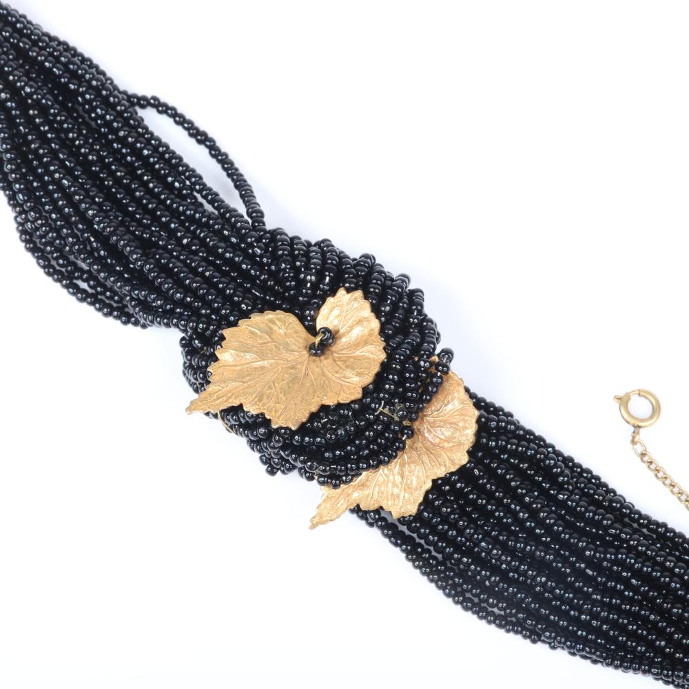 "Miriam Haskell 24-strand ruby glass bead necklace with gold tone pendant leaf, with coordinating bracelet with black glass beads. 16""L (necklace)"