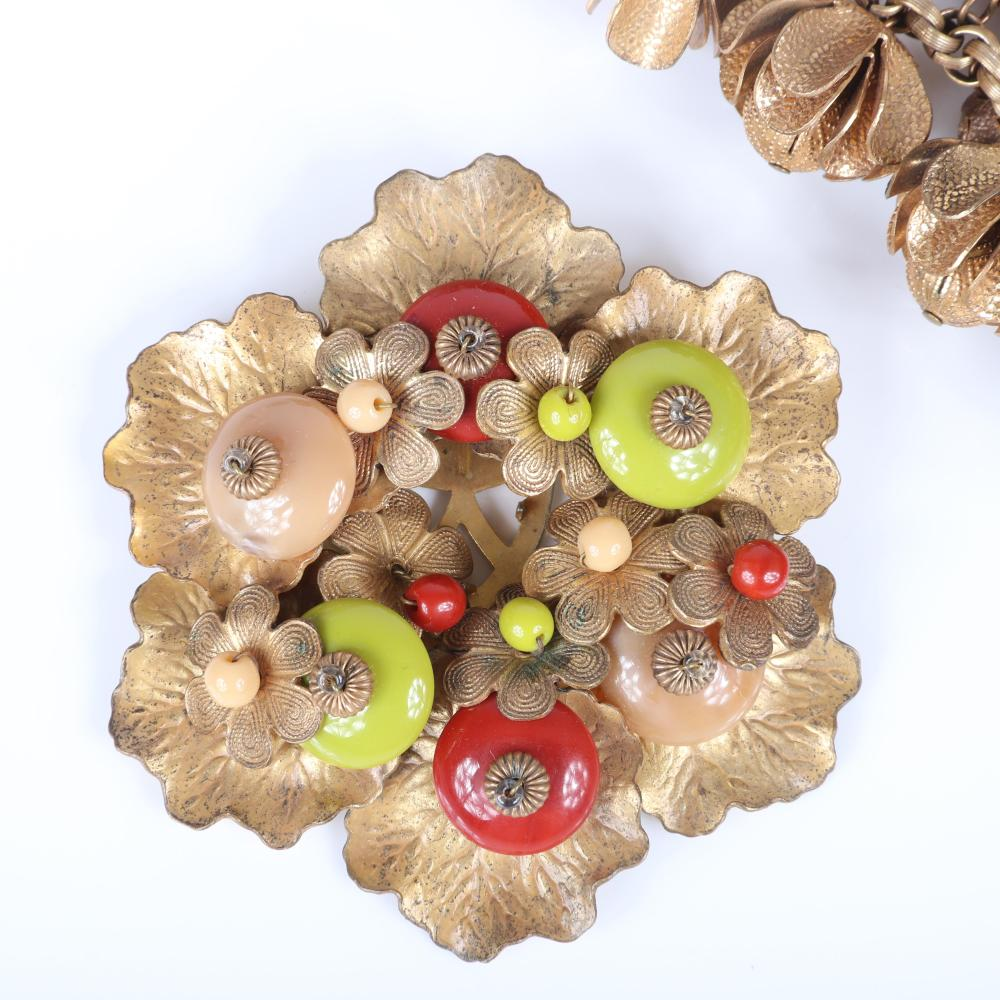 """Miriam Haskell 3pc brass group: bracelet with dangling flower cups, gold tone flower earrings, and large flower and leaf brooch with green and red glass disk beads. 7 1/2""""L (bracelet), 2 3/4""""diam (brooch)"""