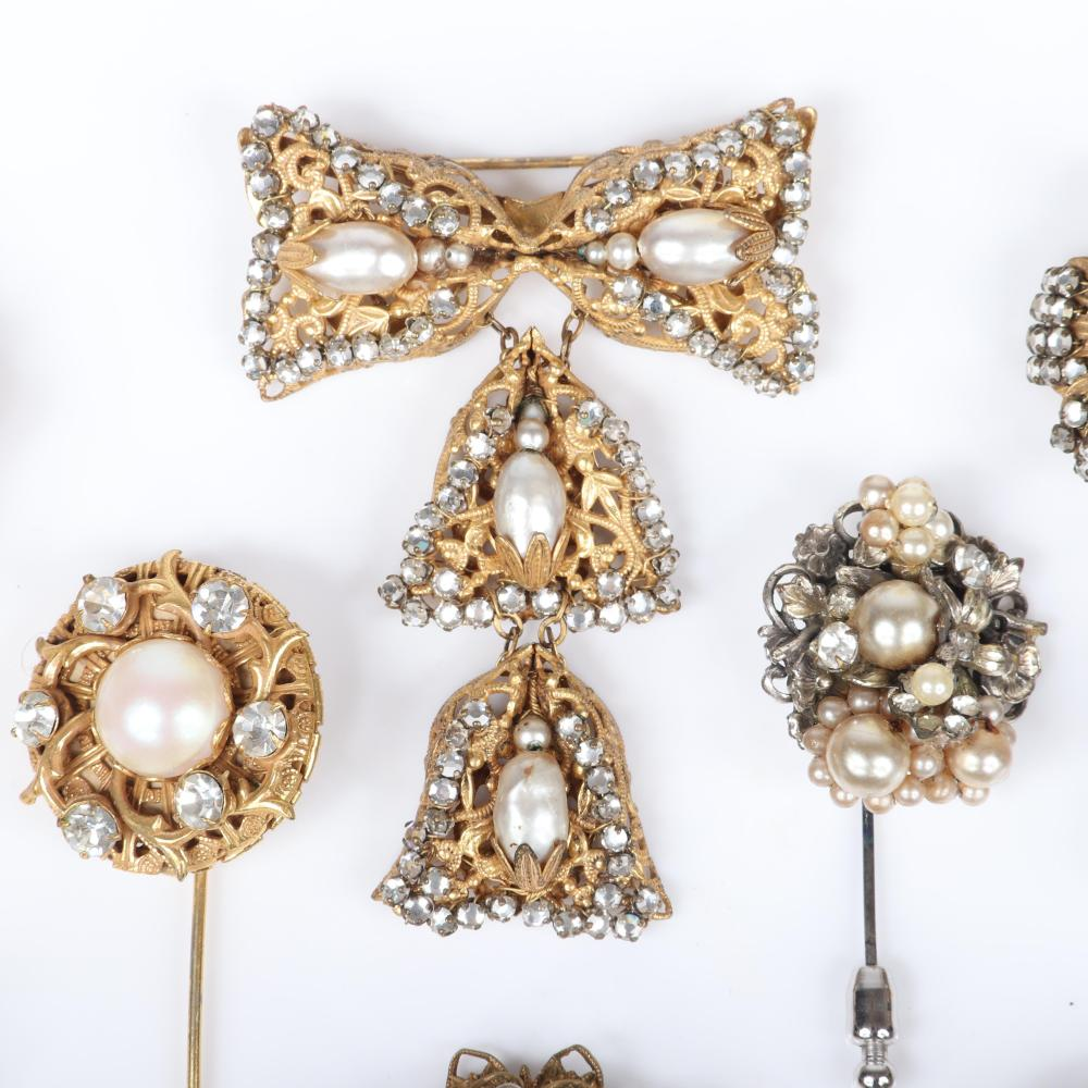 """Miriam Haskell 8pc faux pearl, rhinestone and filigree group: dangling bow pin, four hat stick pins, and three pairs of flower earrings. 2 3/4"""" x 2"""" (bow brooch)"""