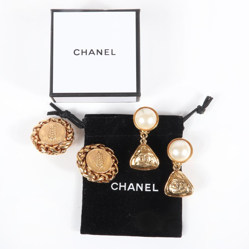 "Two pairs of Chanel designer earrings: gold tone wheat medallion edged in chain and faux pearl with triangular CC logo drop, with original box and felt pouch. 2""H (pearl), 1 3/4""diam (wheat)"