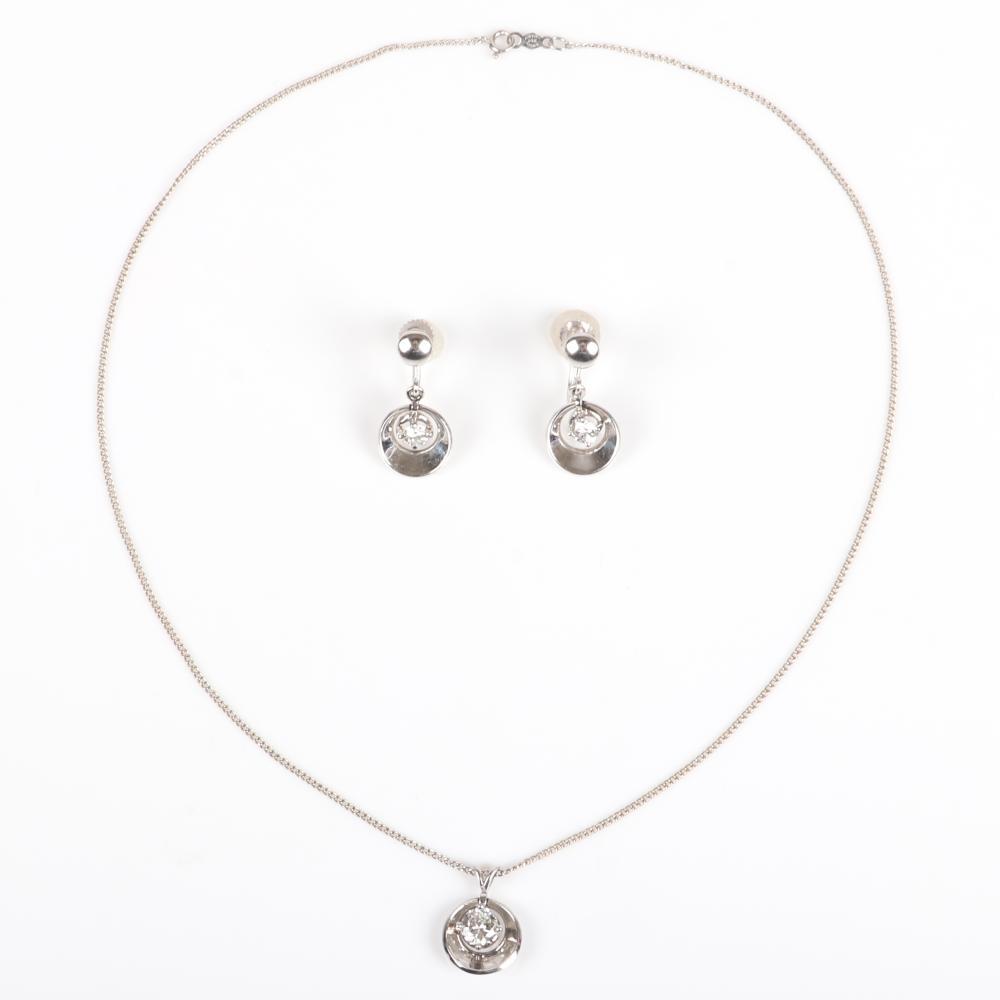 "White gold 14K solitaire diamond pendant necklace and screw back drop earrings set in modernist dangle surround setting. 16""L, 1/2""W x 1/2"" diam. (pendant) 1"" L (earrings) 5.35 dwt"