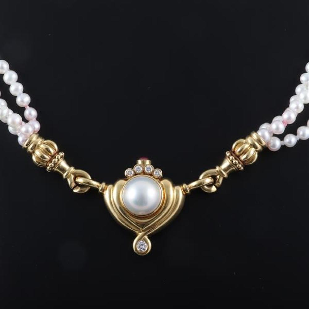 "Lagos three strand pearl necklace with 750 18K yellow gold mabe pearl pendant containing accent diamonds and ruby cabochon. 19""L"