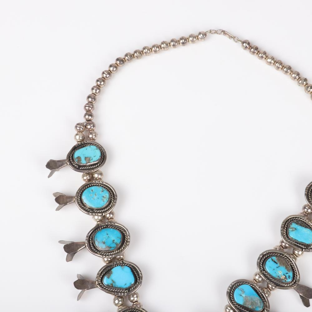 """Native American sterling silver Indian Squash blossom necklace with 17 turquoise cabochons and blossoms suspended on double rows of hand-made silver beads. 23""""L"""