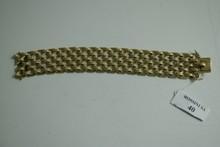 Bracelet large et articulé en or jaune ajouré à décor de croisillons.  Longueur: 19cm.  Poids: 78g.