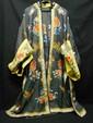 Robe ouvrant par le milieu, en soie damassée grise brodée au fil polychromes et dorés de fleurs et papillons ; le revers des manches en soie jaune. Chine. (petits accidents).