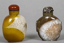 Two Chinese carved mineral snuff bottles and stoppers One stopper carved.  The larger 8 cm high.  (2)
