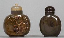 Two Chinese carved agate snuff bottles and stoppers The larger worked with a sage.  The larger 7 cm high.  (2)