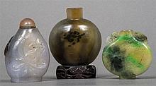 A Chinese agate snuff bottle Of typical rounded form, mounted on a pierced wooden plinth base; together with two further snuff bottles.  The former 7.5 cm high.  (3)