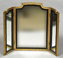 A 19th century carved giltwood framed triptych dressing table mirror Of twin hinged section form, with arched top and ebonised slip.  83 cm high.
