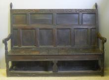 A 17th century carved oak settle The panelled back with turned finials and