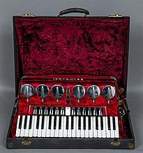 A Scandalli piano accordion  Of typical form, in mottled red casing, housed