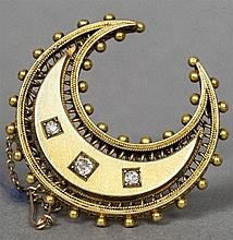 An unmarked 18 ct gold and diamond set brooch Of crescent form set with thr