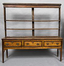 A George III oak dresser  The open rack above three crossbanded drawers wit