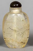 A rock crystal snuff bottle Of typical ovoid form with a brown glass lid.  6.75 cm high.