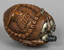 A 19th century carved coquilla nut snuff bottle Carved with the heads of three dignitaries.  8 cm long.