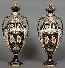 A pair of Royal Crown Derby porcelain vases and covers Each typically decorated in the Imari palette with twin scrolling gilt heightened loop handles above the ovoid body, standing on a stepped spreading plinth base.  Each 40 cm high.